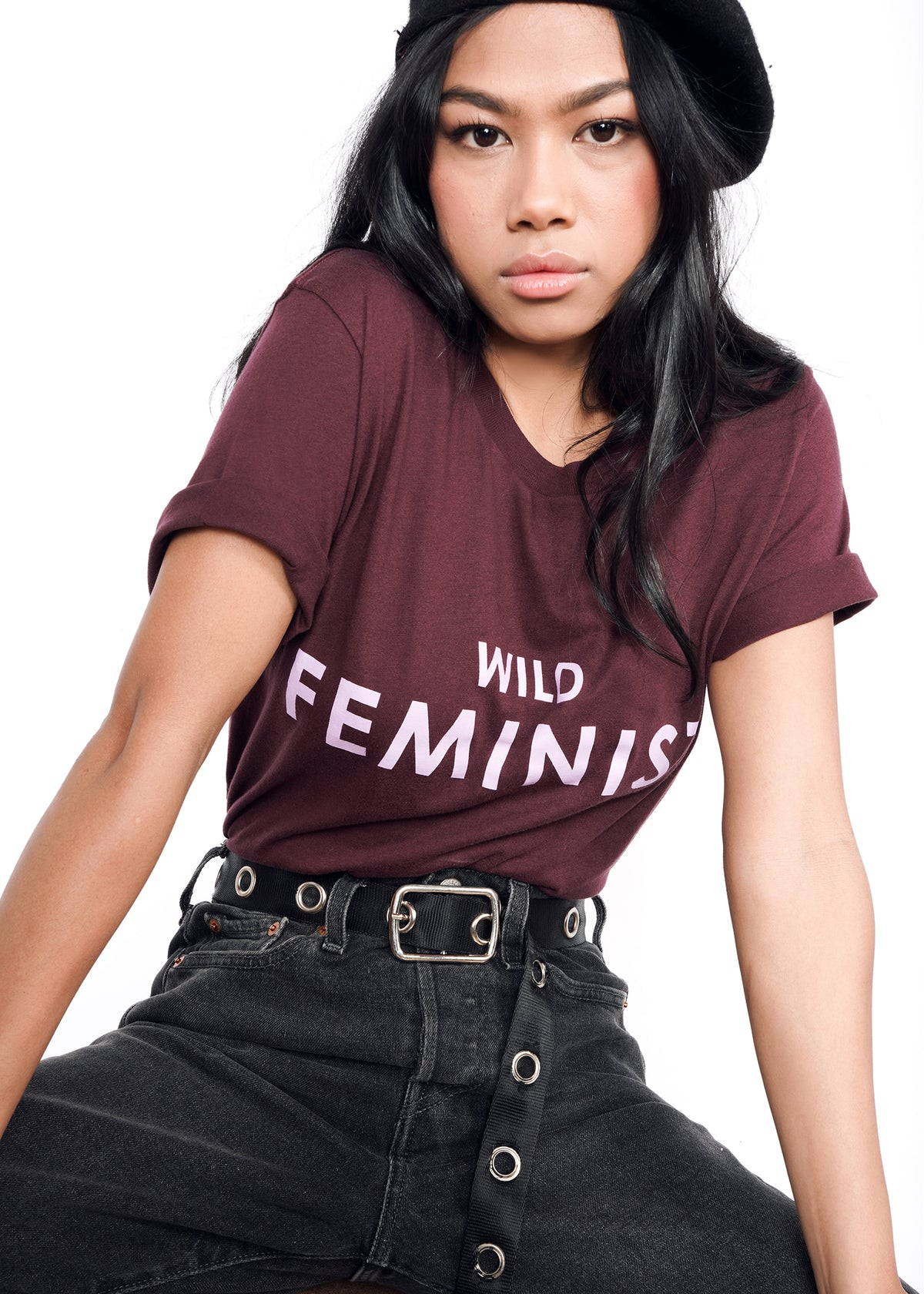 "Model wearing burgundy merlot graphic tee in size XS that reads ""WILD FEMINIST"" in light lavender"