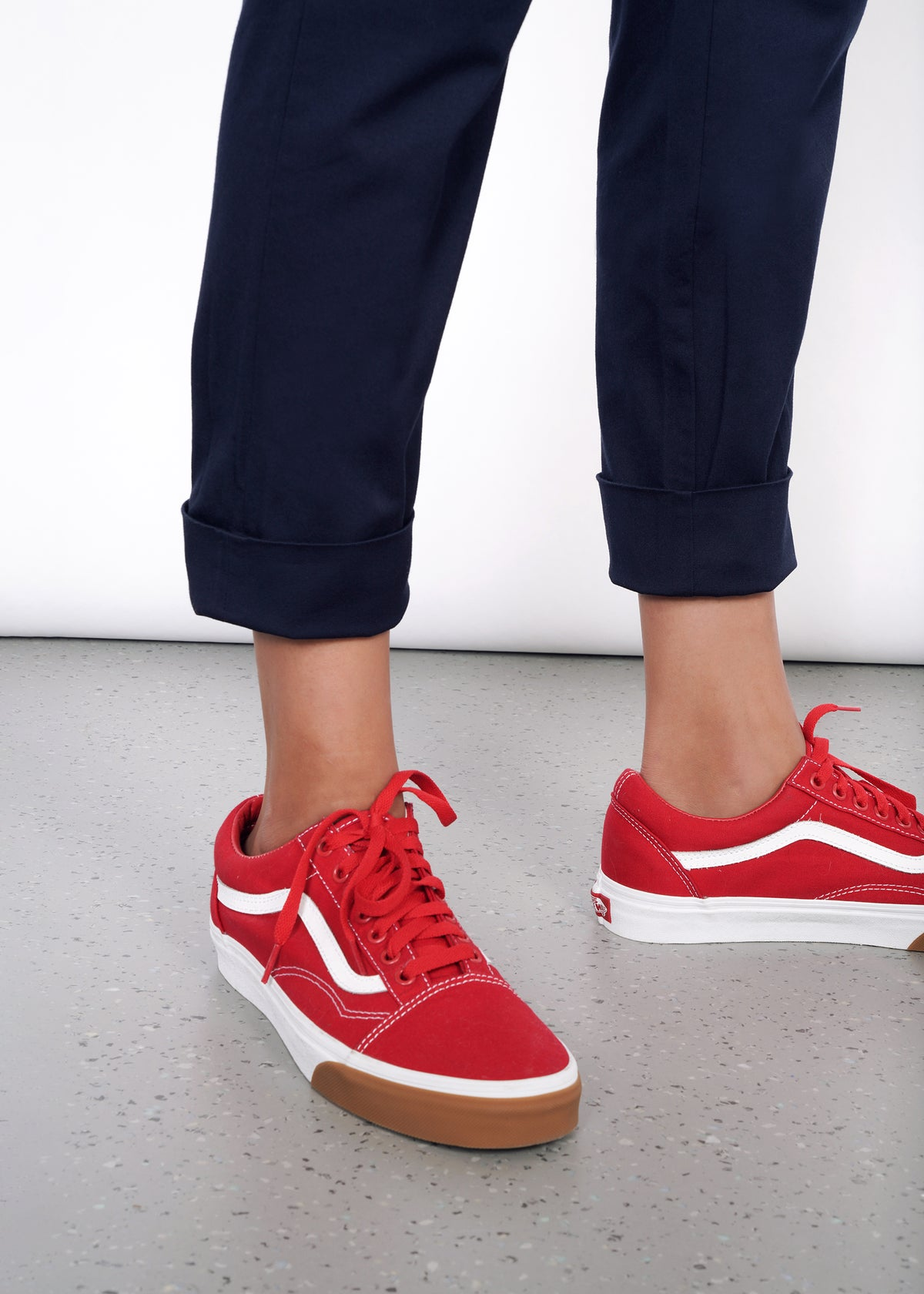 Pant leg cuff on navy trouser pant, cuffed once cleanly and worn with red vans