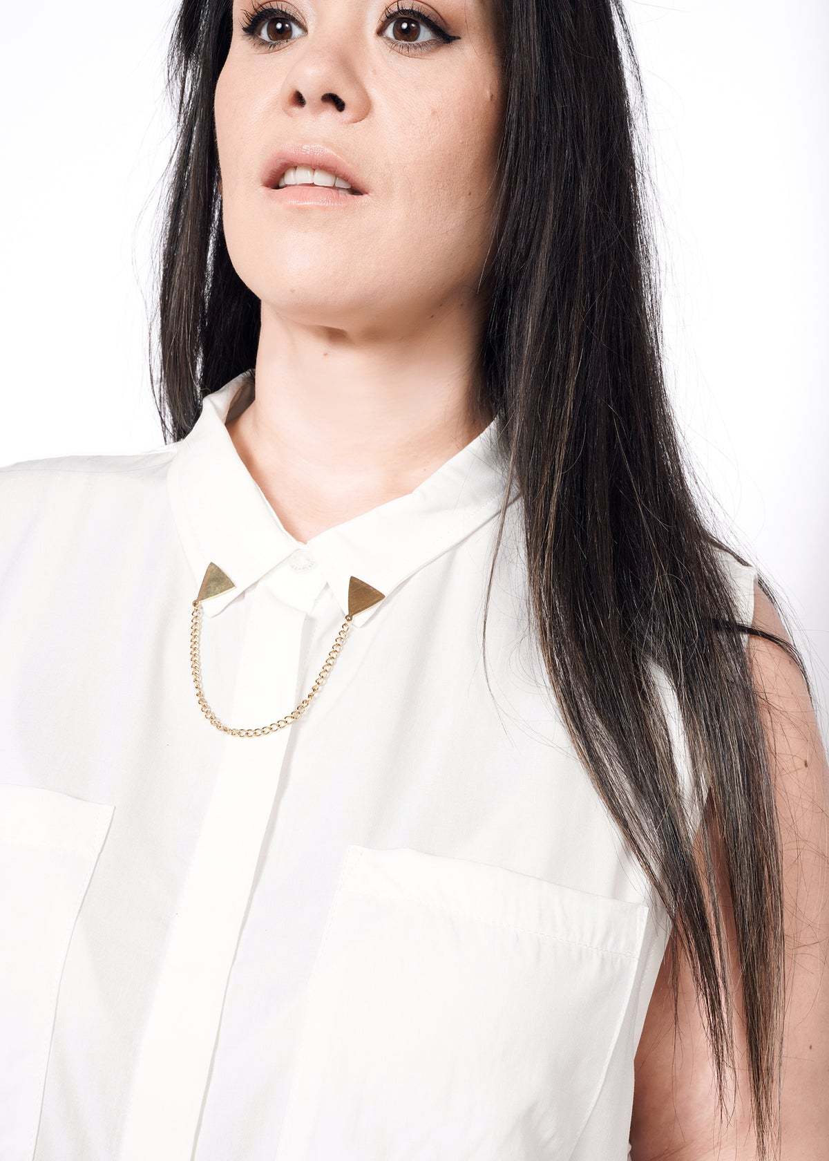 Model wearing white sleeveless drapey button up shirt in size XXL with metal collar tips accessory at collar