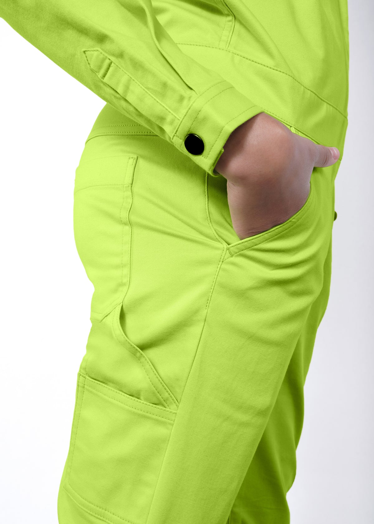 Model wearing neon green long sleeved essential coverall jumpsuit in size small, hand in pocket showing side leg pocket and butt pocket
