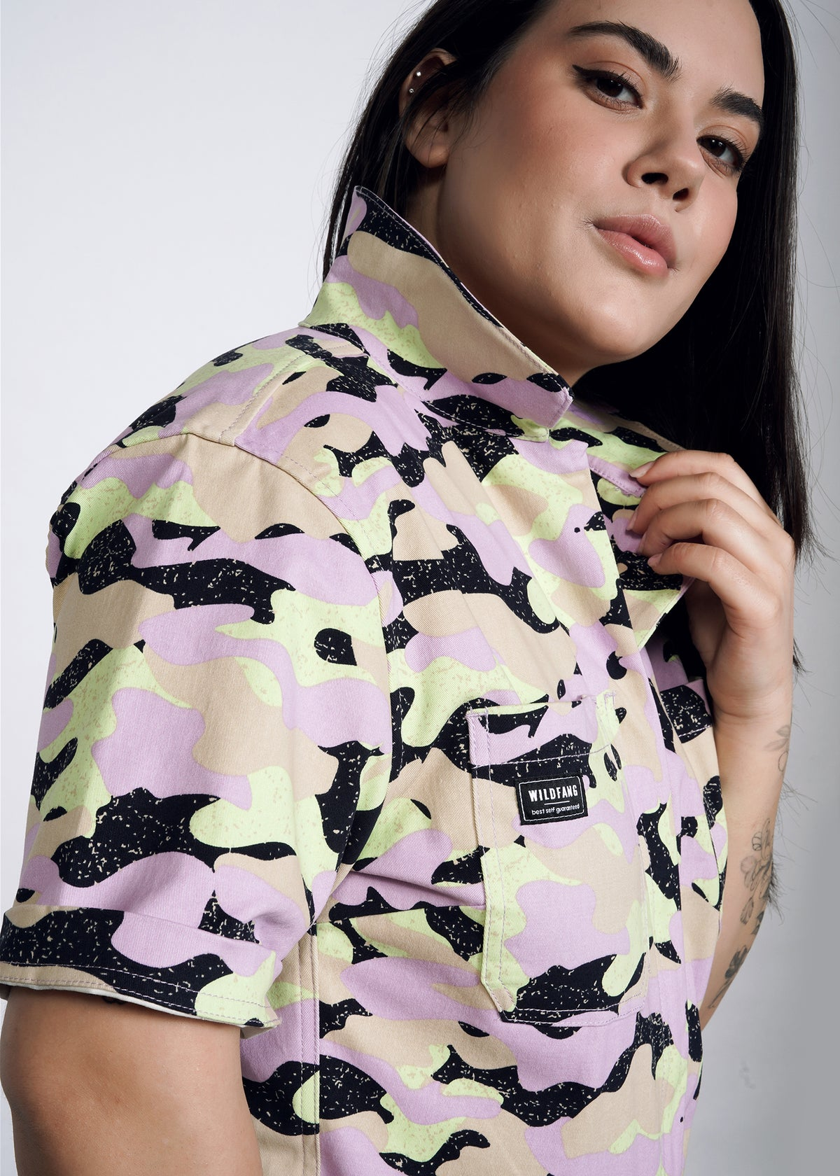 Model wearing lavender, celadon, black, and tan camouflage all over print short sleeve coverall jumpsuit in size L, collar popped and sleeves cuffed once. Front chest pocket detail shown