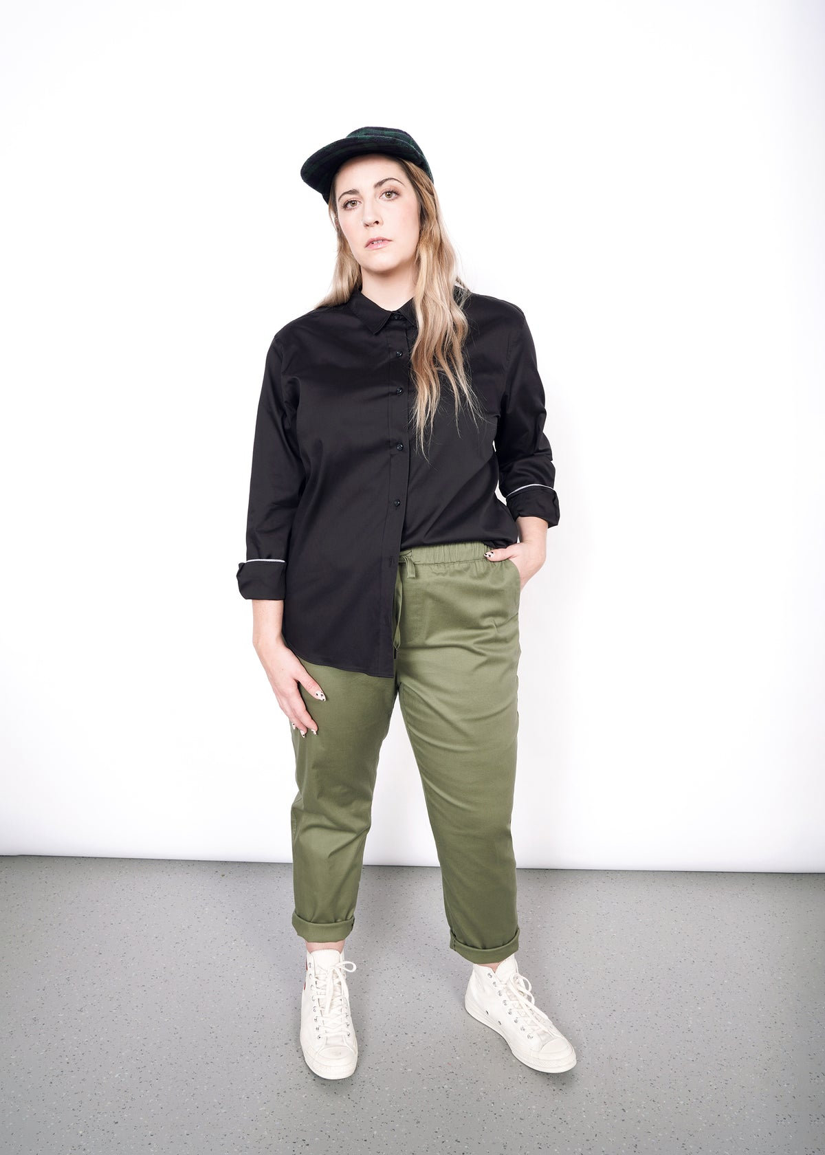Model with long hair and hat wearing black long sleeve button up shirt and olive drawstring pants, white high top sneakers