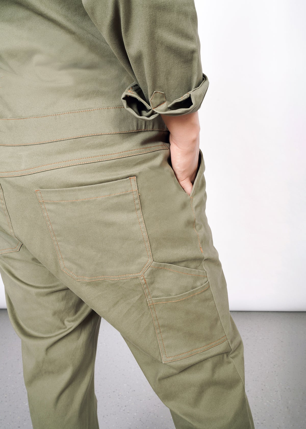 closeup of hand in front right hand pocket of olive coveralls. Shows additional side and butt pockets with orange stitching