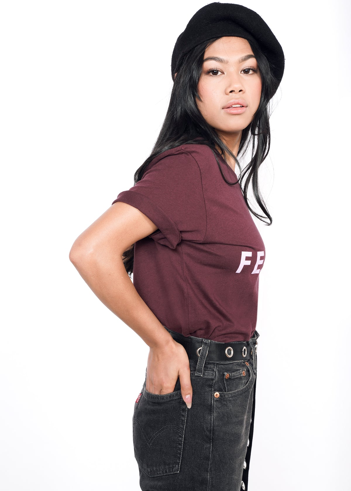 Side view of model wearing burgundy merlot graphic tee in size XS, with hands in back pockets of black Levi's