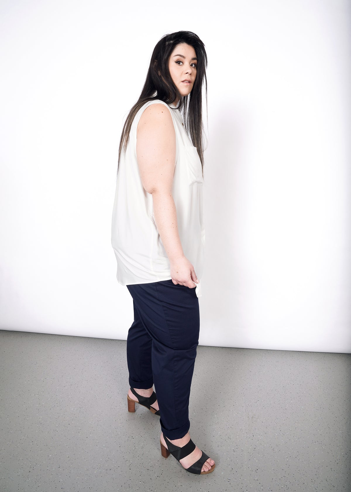Model wearing white sleeveless drapey button up shirt in size XXL with navy trouser pants and heels