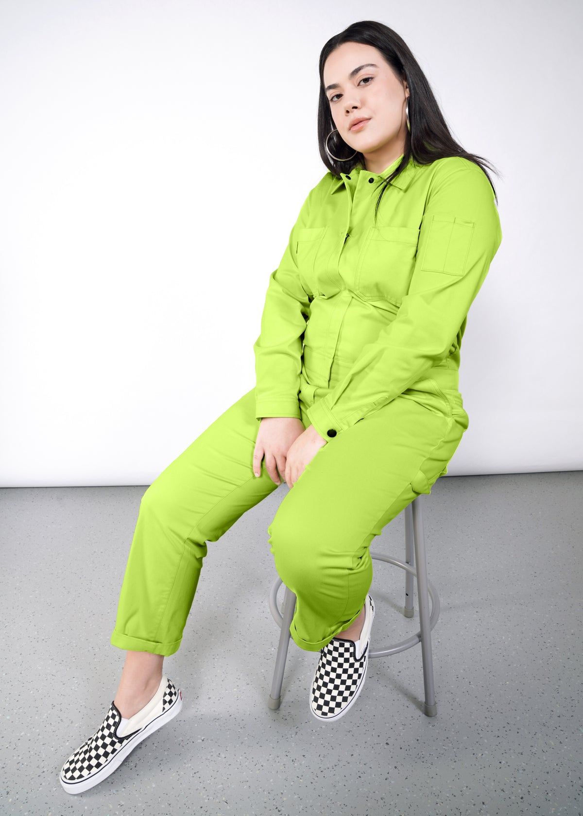 Model wearing neon green long sleeved essential coverall jumpsuit in size large, sitting on stool