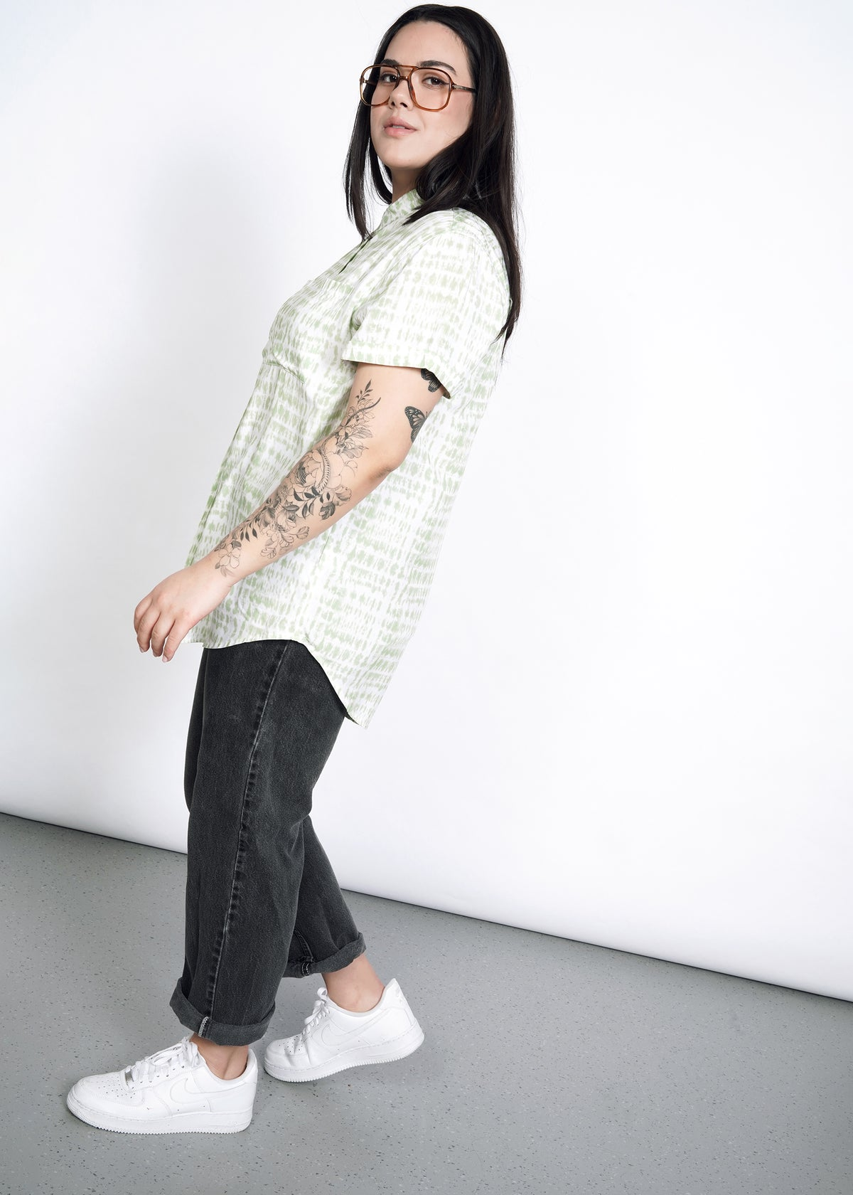 Side view of model wearing celadon shabori button up, with glasses, white sneakers, and black jeans, cuffed.