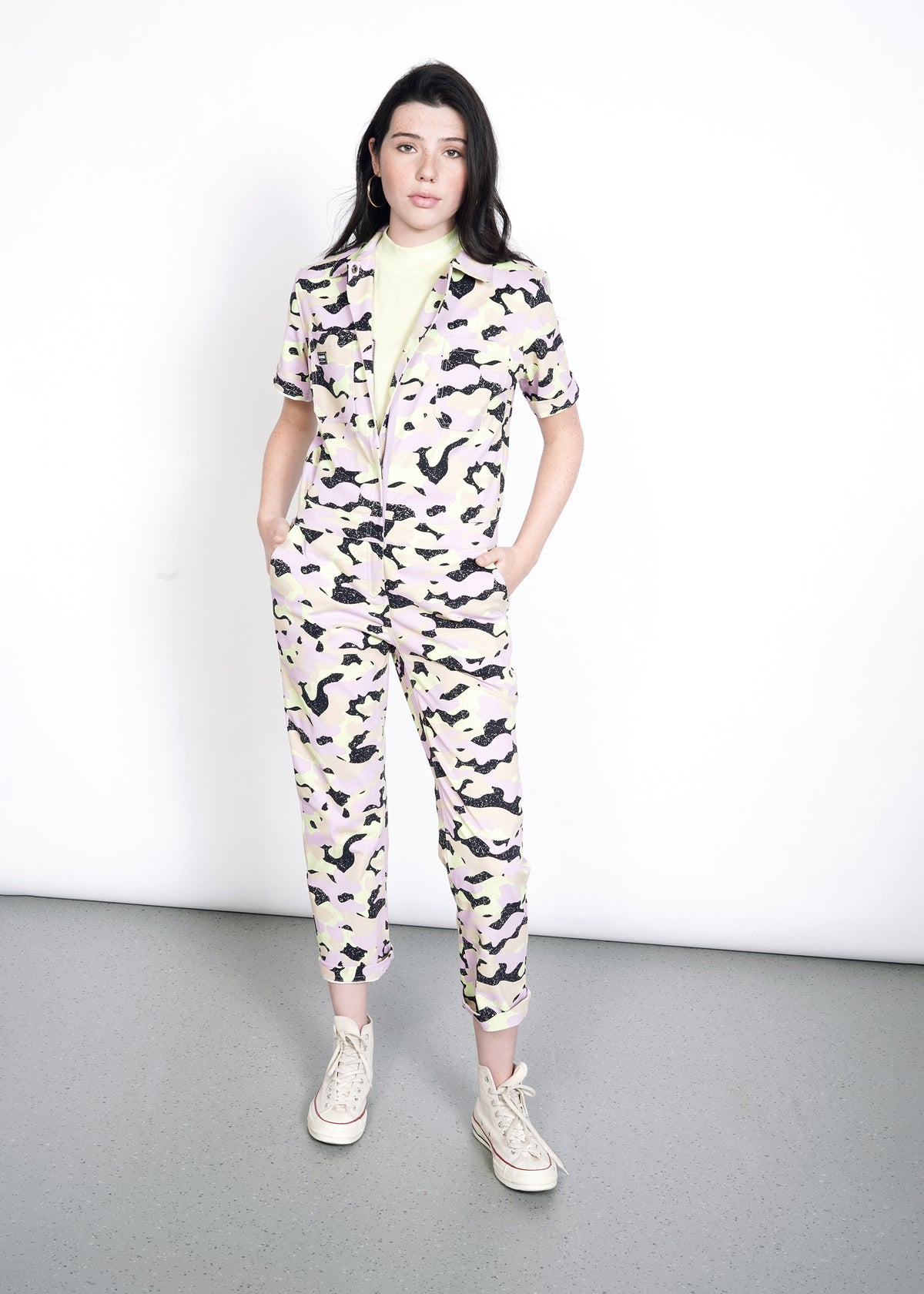 Model wearing lavender, celadon, black, and tan camouflage all over print short sleeve coverall jumpsuit in size S, with hands in pockets and green tank underneath