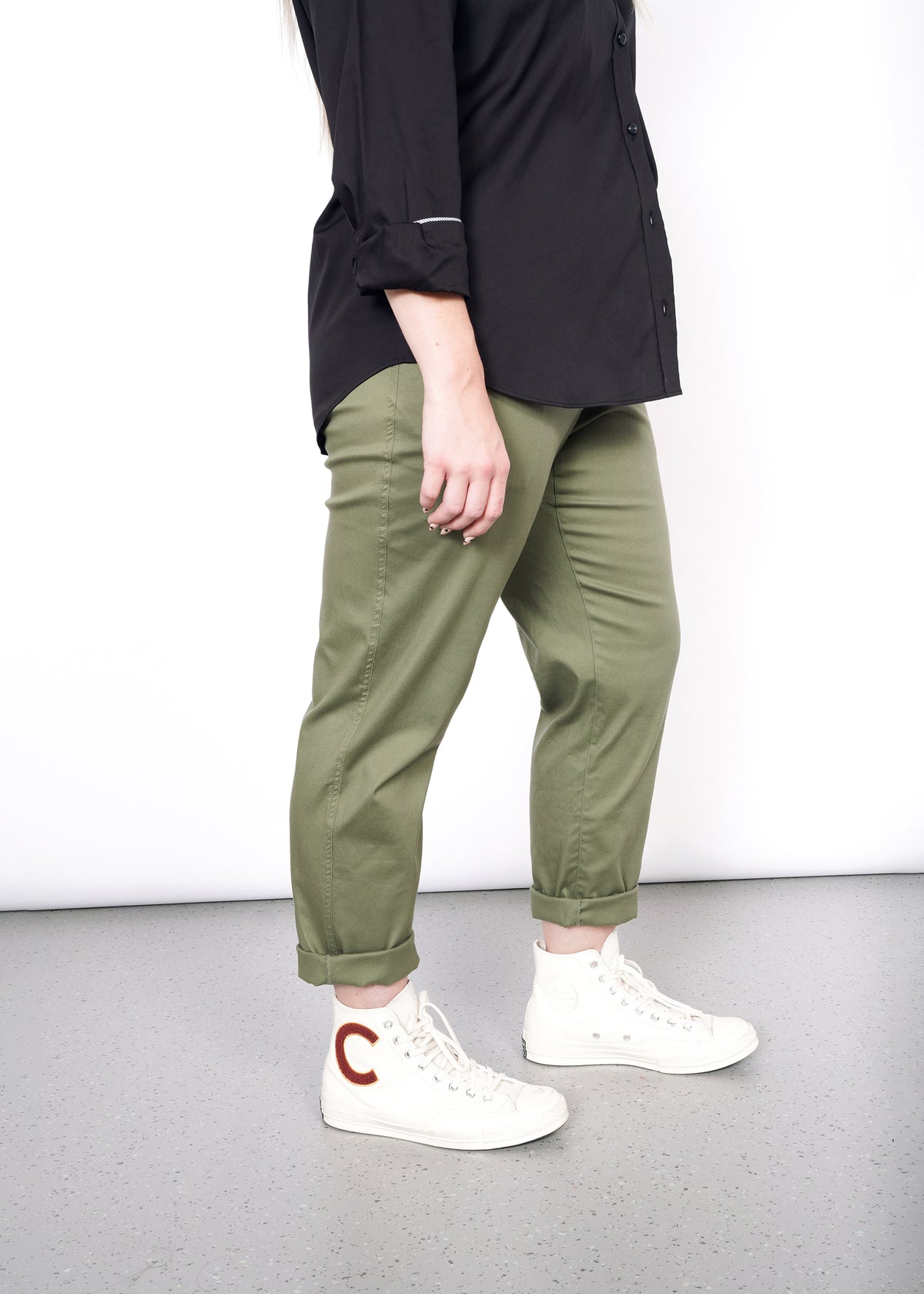 Side view of waist down model wearing olive pants, white sneakers, and black button up shirt