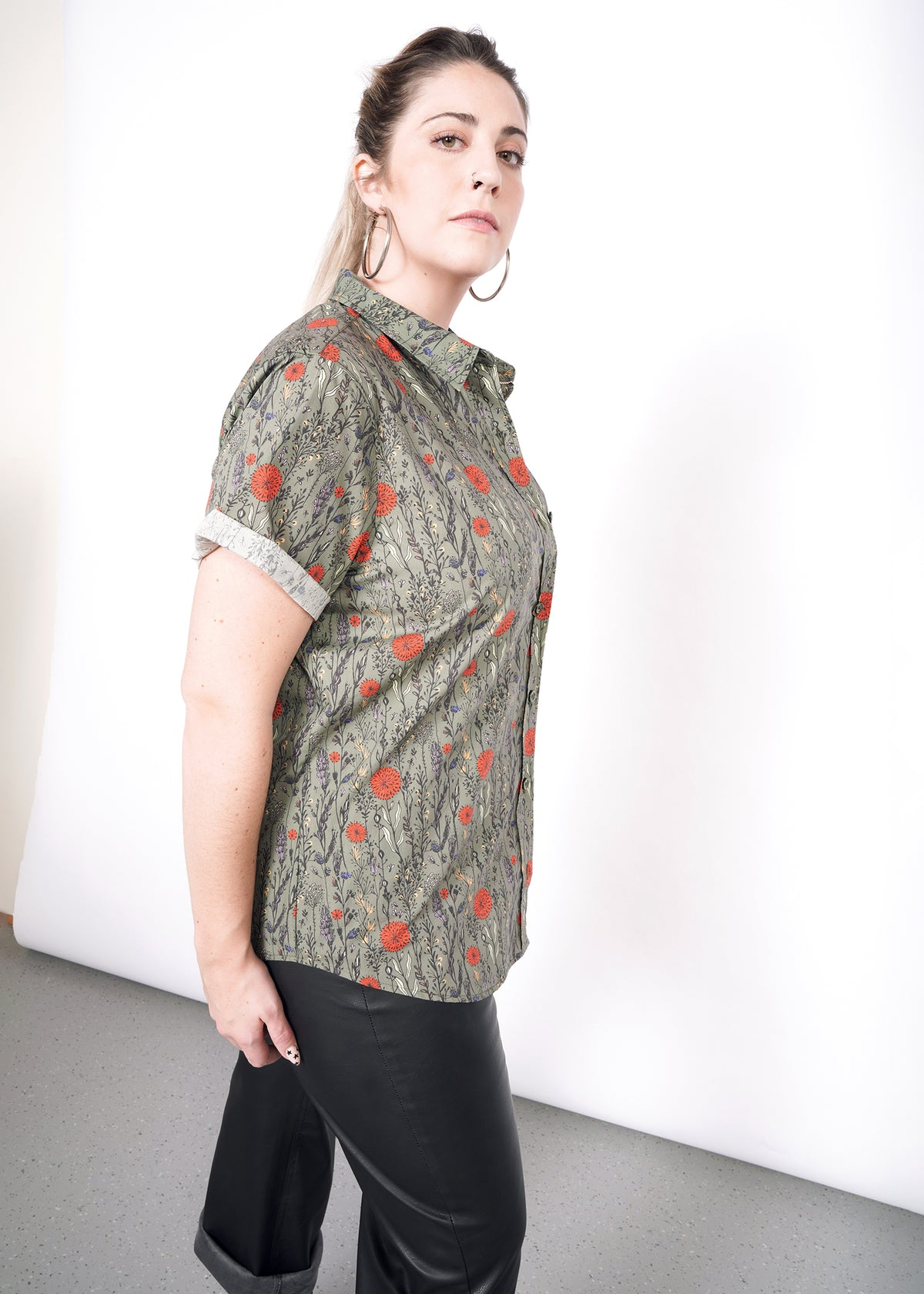 Model wearing botanical all over printed short sleeved button up shirt in size XL, with the sleeves cuffed