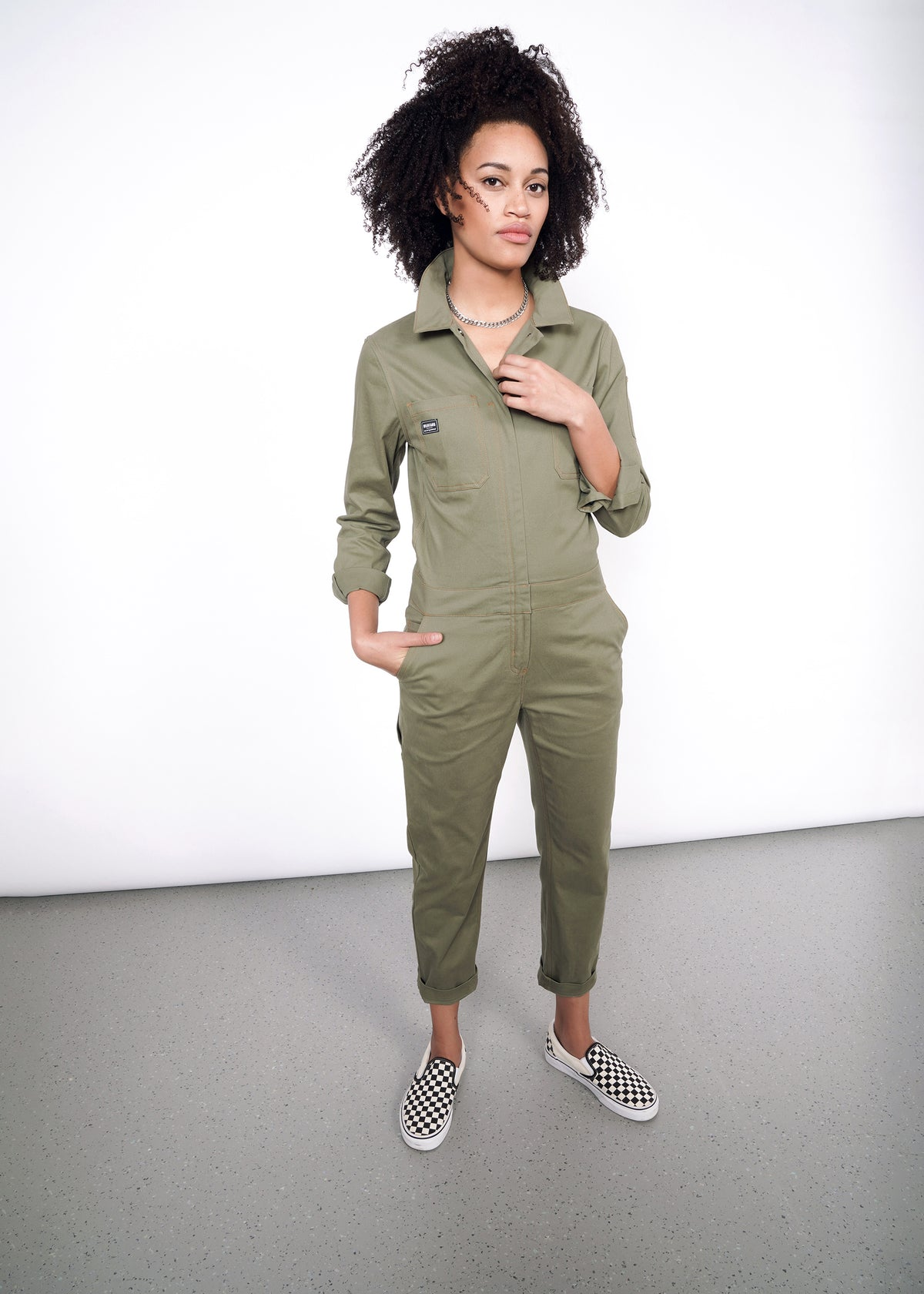 Model wearing olive coveralls slightly unzipped with no shirt underneath, styled with a silver necklace and vans. Coverall legs are cuffed once.