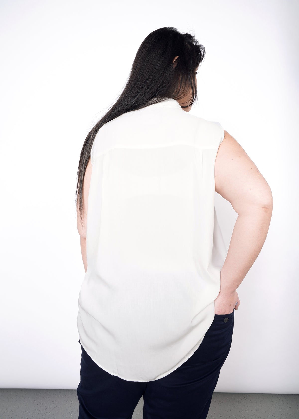 Backside of model wearing white sleeveless drapey button up shirt in size XXL, with one hand in back pant pocket