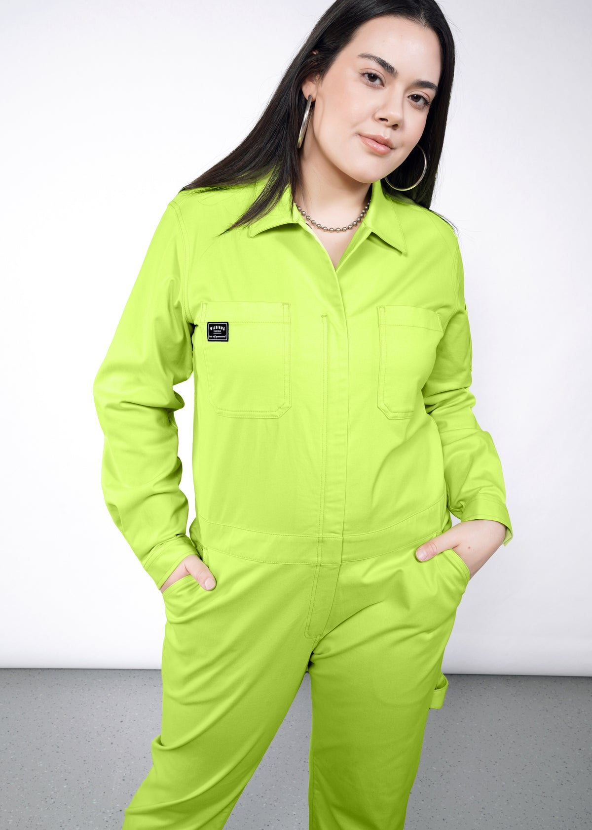 Model wearing neon green long sleeved essential coverall jumpsuit in size large, with hands in pockets