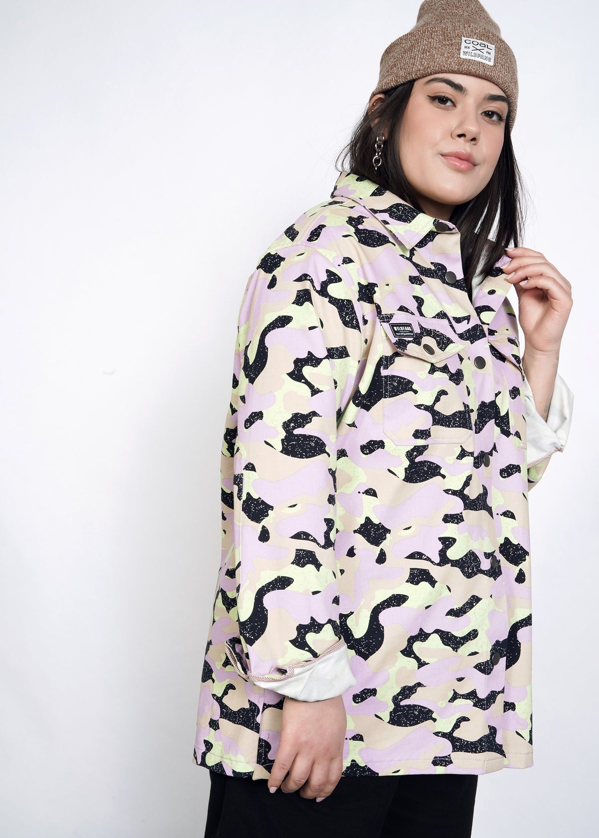 Model wears lavender, celadon, and black camouflage all over print shirt jacket (shacket) in size large with brown beanie