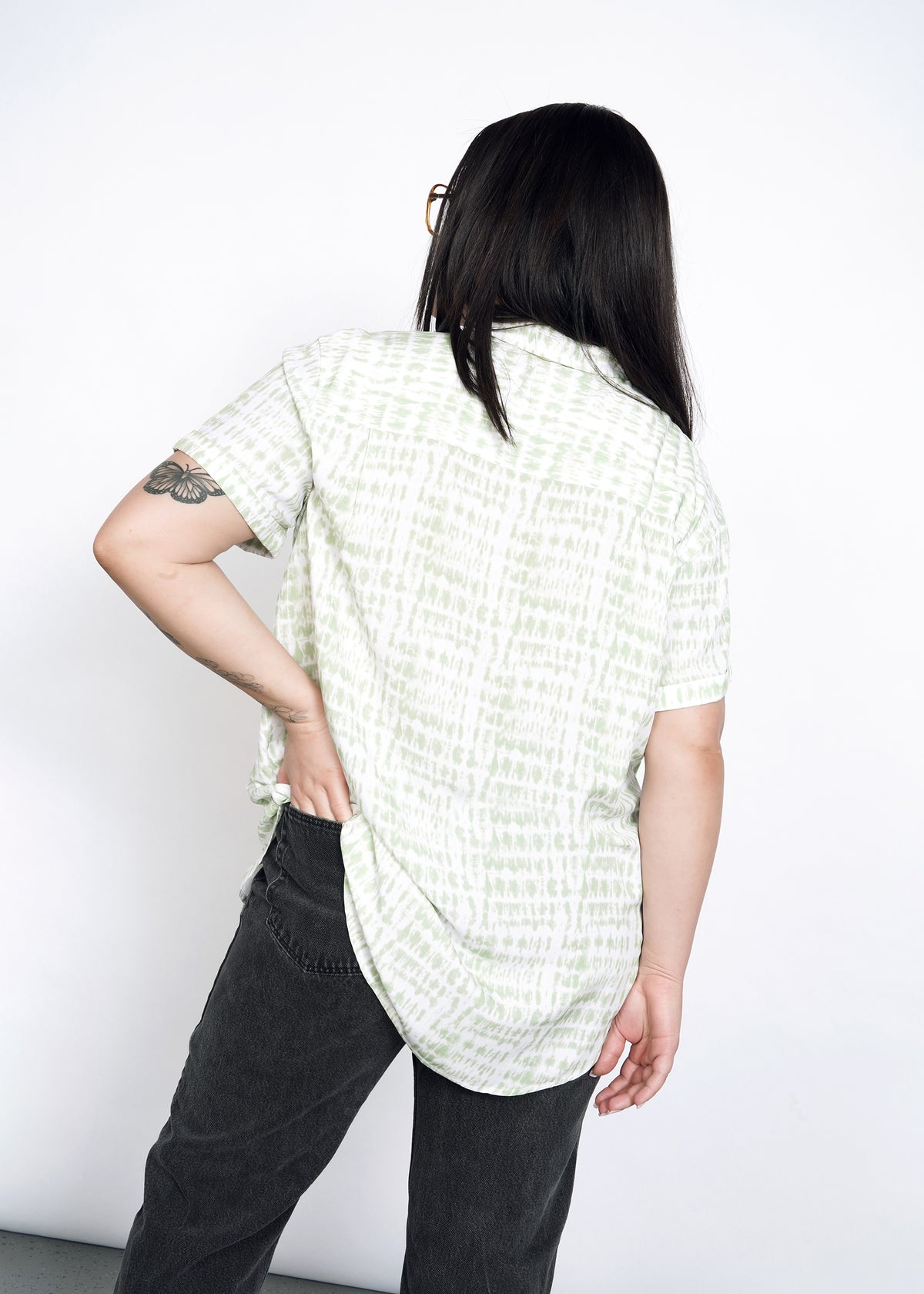 Back view of model wearing size L celadon shabori short sleeve button up, with one hand in back black jean pocket