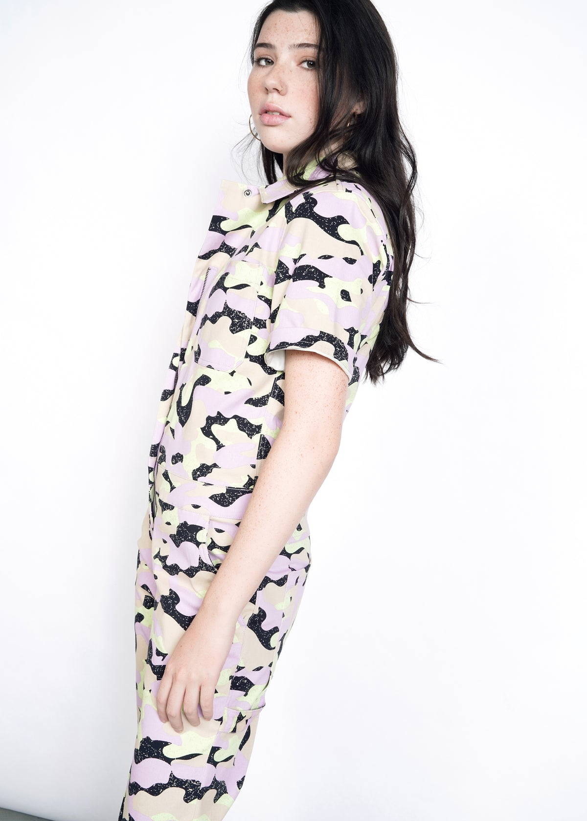 Model wearing lavender, celadon, black, and tan camouflage all over print short sleeve coverall jumpsuit in size S