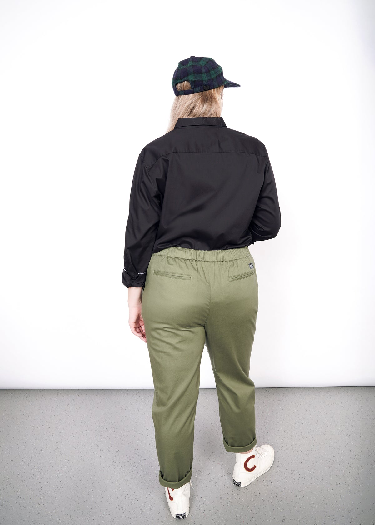 Model facing away form camera, black shirt tucked in to show butt of olive drawstring pants