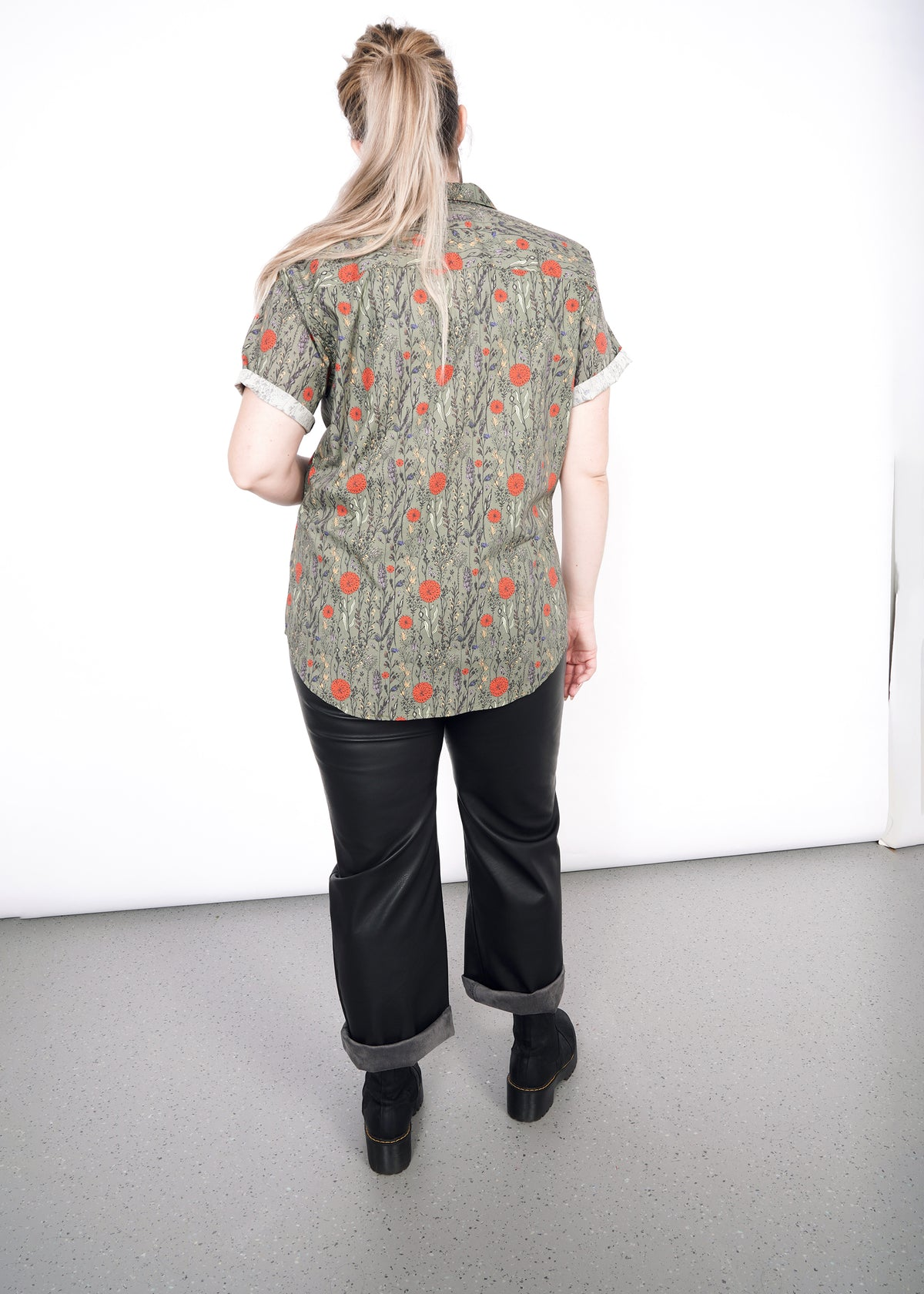 Back view of model wearing botanical all over printed short sleeved button up shirt in size XL, with the sleeves cuffed, styled with black pants and boots