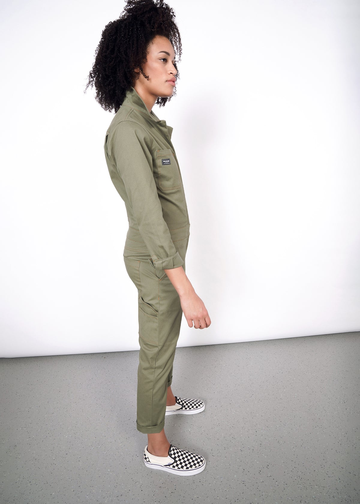 Model wearing olive coverall in size small, showing side body view