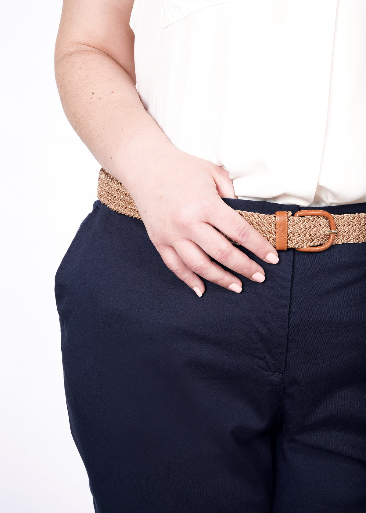 Waist with tan belt on navy trouser pants, with white sleeveless top tucked in