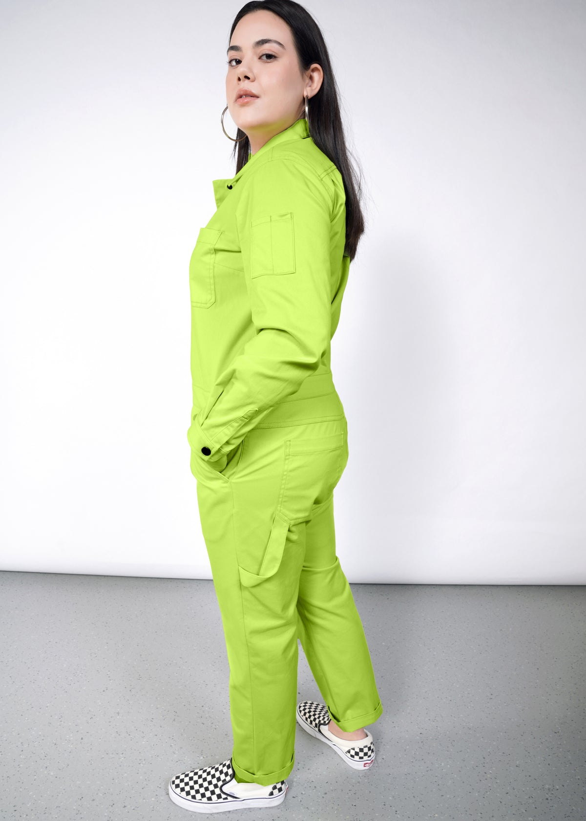 Model wearing neon green long sleeved essential coverall jumpsuit in size large, with hands in pockets, facing left