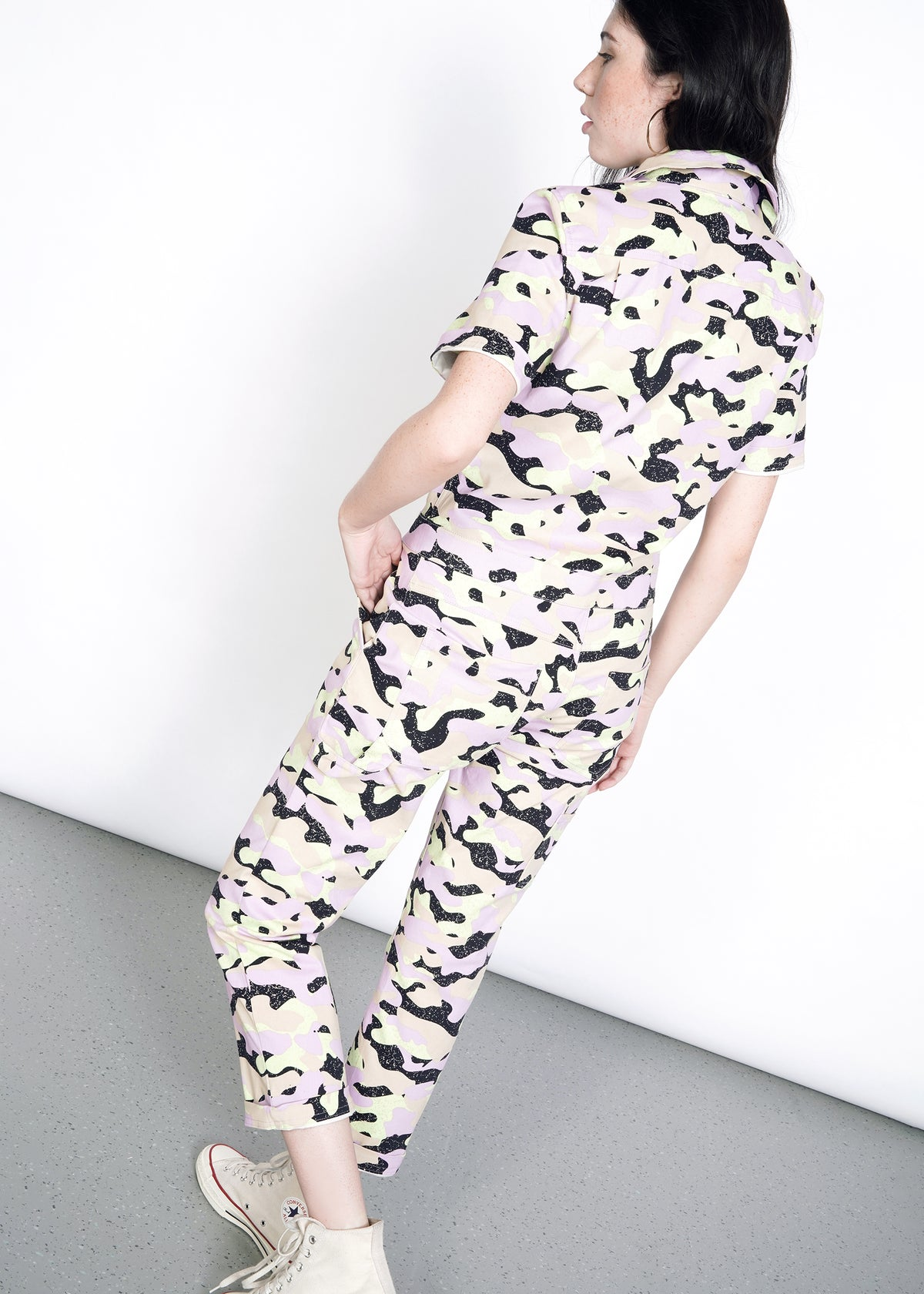 Model facing away, wearing lavender, celadon, black, and tan camouflage all over print short sleeve coverall jumpsuit in size S, pant legs cuffed once and worn with white converse