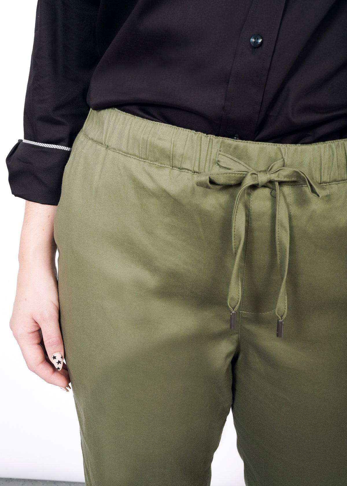 Closeup of waistband and drawstring on olive pants