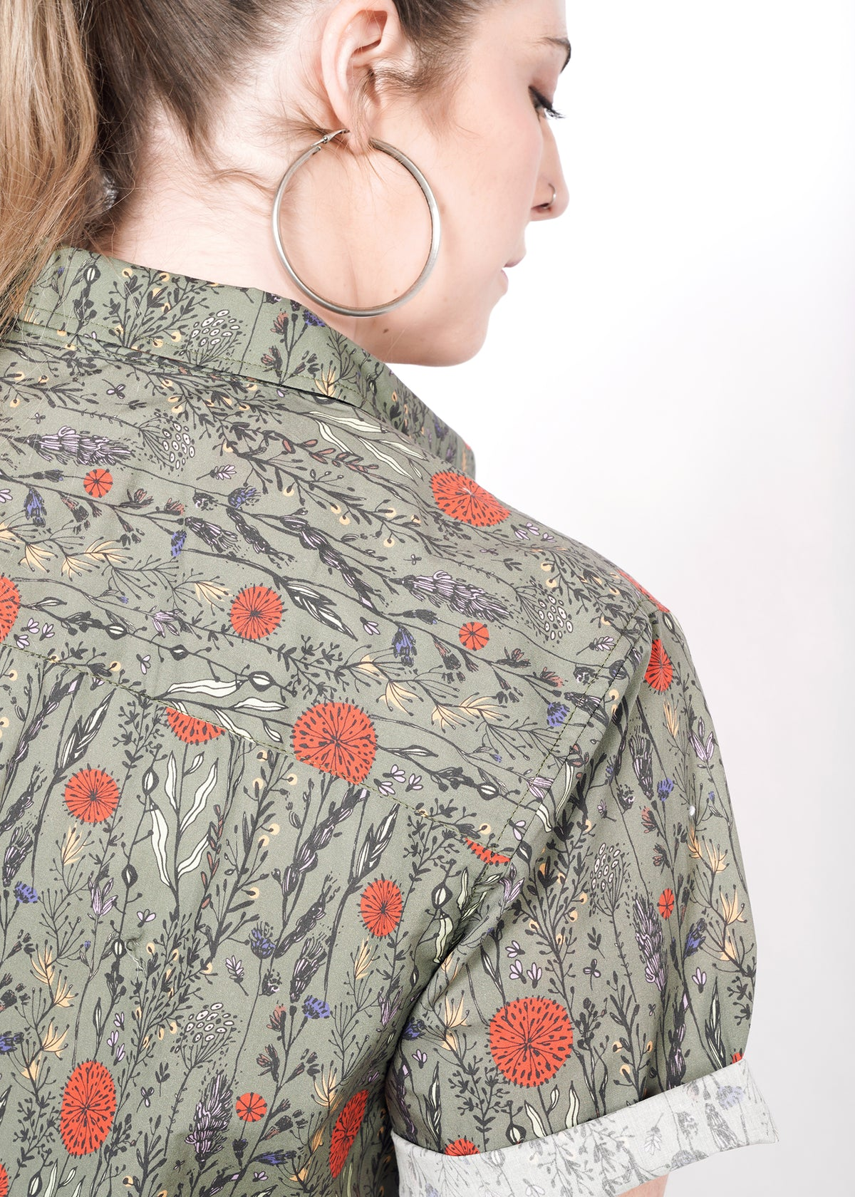 Detail of the pattern on the button up- a botanical print with red, yellow, and purple flowers and plants on light olive green background