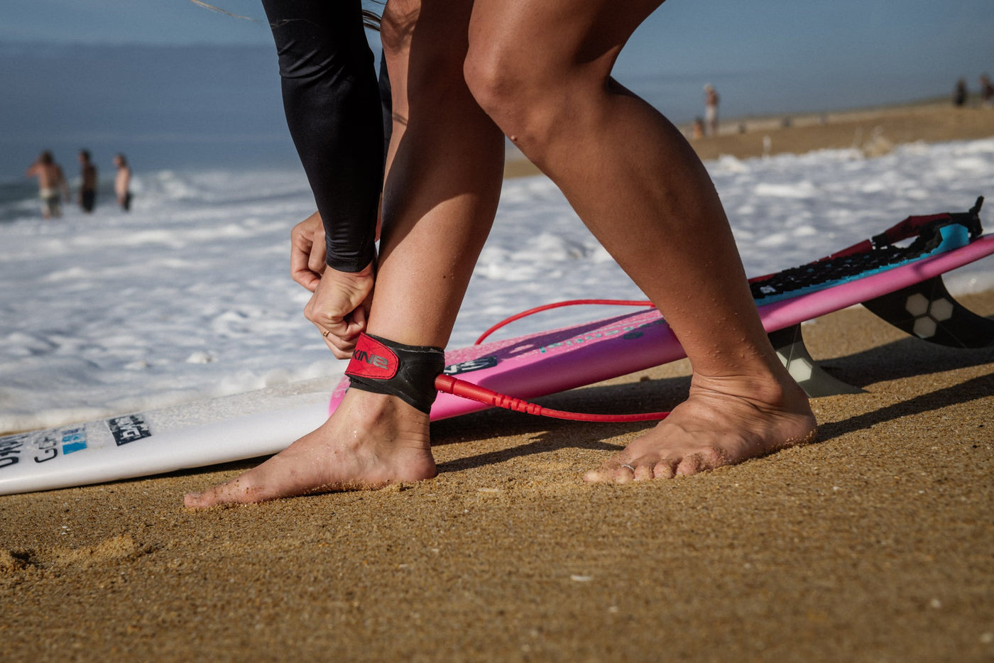 Woman attaching her Dakine Surf Leash before surfing.