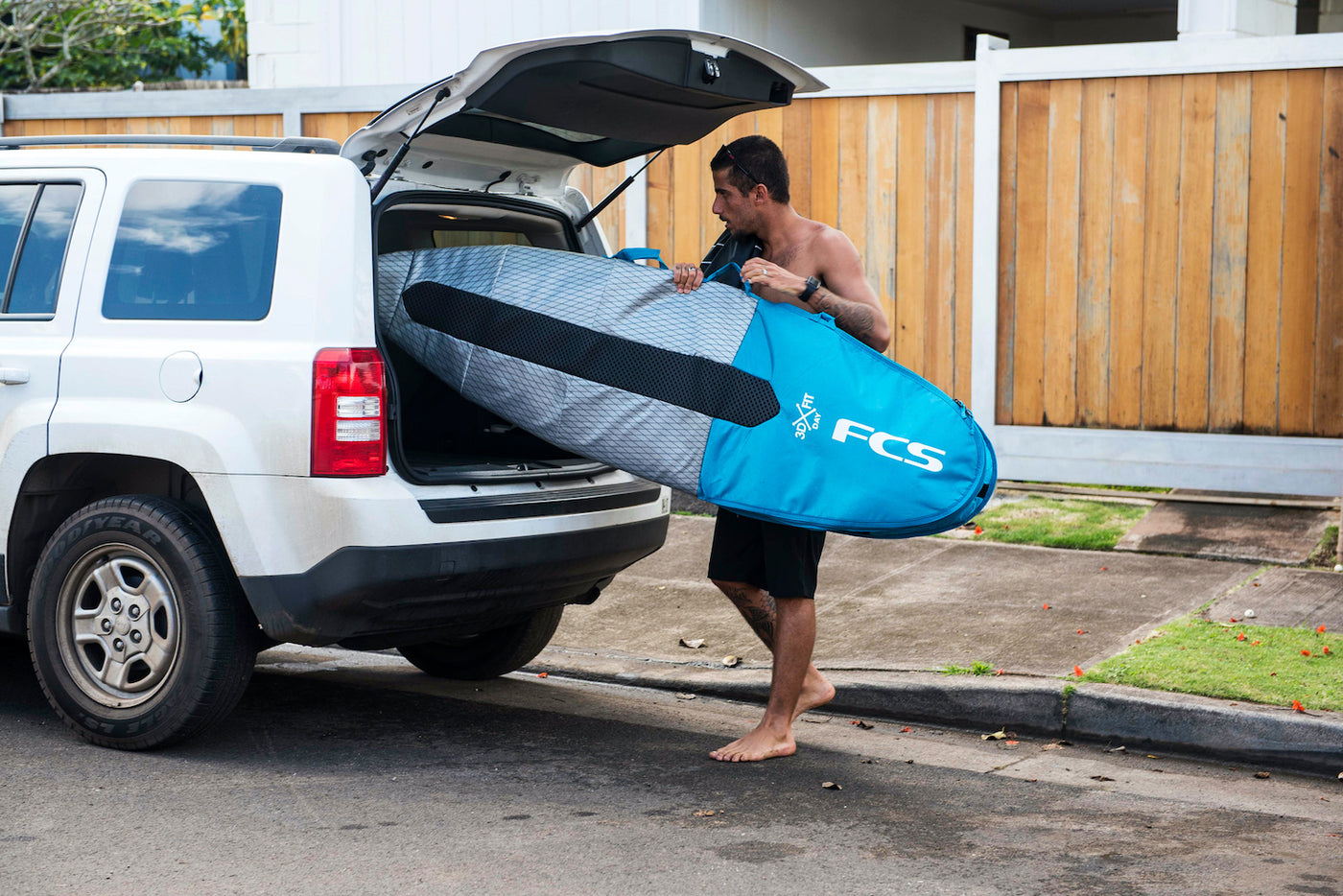Man carrying surfboard in a FCS Surboard bag cover.
