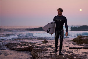 Man in wetsuit at sunset after surfing in Ireland.