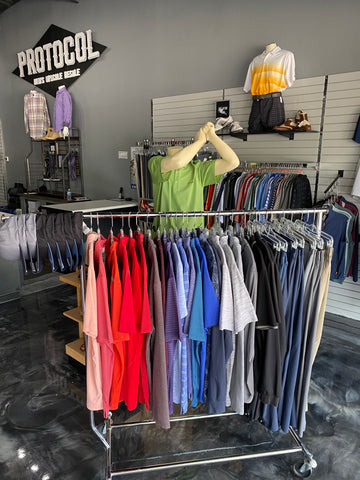 A collection of golf shirts organized by color in front of a golf display. Men's clothing plano tx, men's designer clothing, men's designer clothing sale, men's consignment, consignment store.