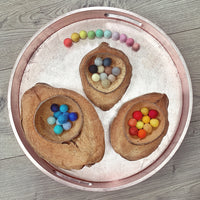 20mm coloured felt balls in ELEMENTS sets inside coconut bowls on a play tray
