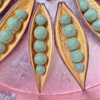 natural pea pod loose parts made from coco boats and green felt balls