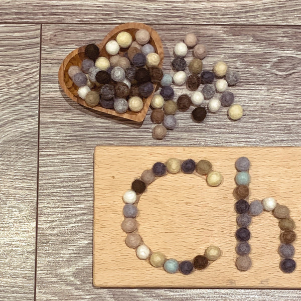 natural earth mini felt balls on a wooden name board
