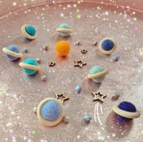 mini planets loose parts made with felt balls and wooden rings, wooden star cutout shapes and a felt ball sun