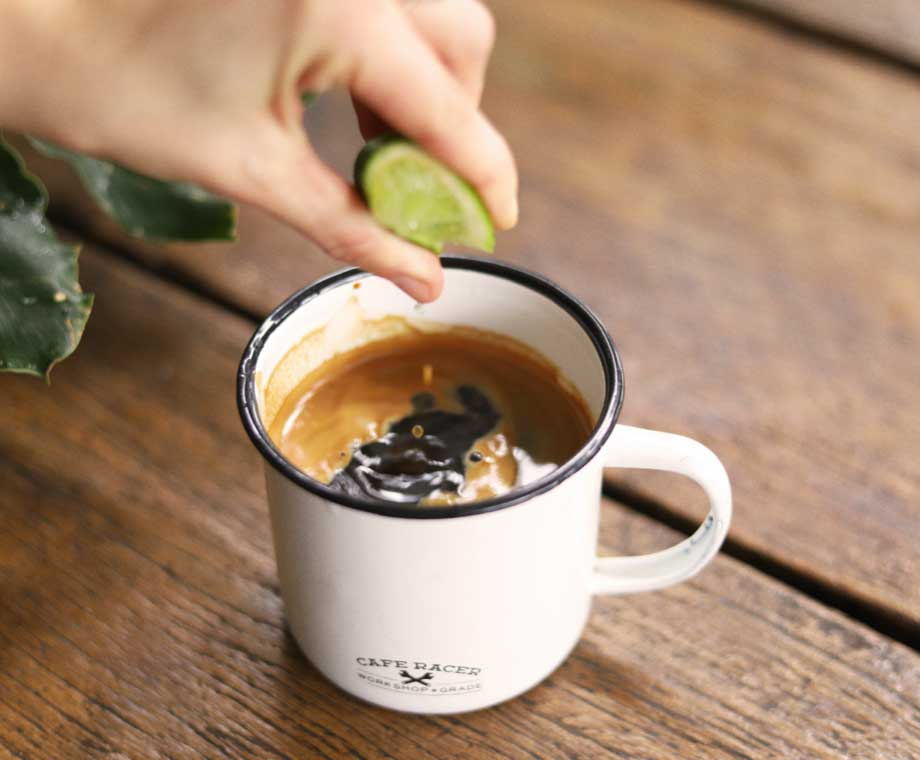 Squeezing lime into PNG coffee