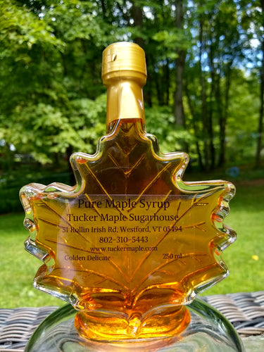 Maple leaf shaped glass bottle filled with maple syrup made by Tucker Maple Sugarhouse