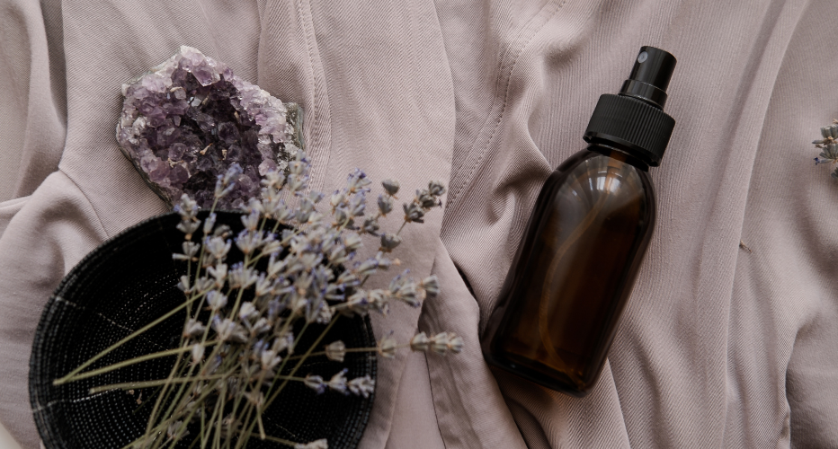 Body Oil in Glass Bottle on White Fabric with Lavender Sprigs