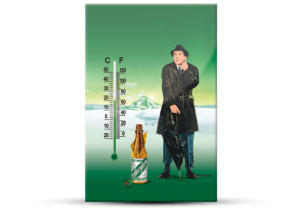 A green thermometer with Celsius and Fahrenheit that displays a man in a jacket and a bottle of Underberg