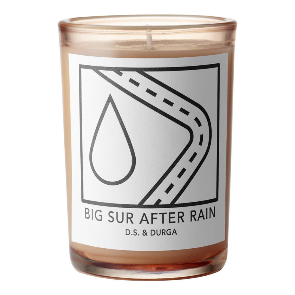 A light pink candle with a white label depicting a raindrop and a highway