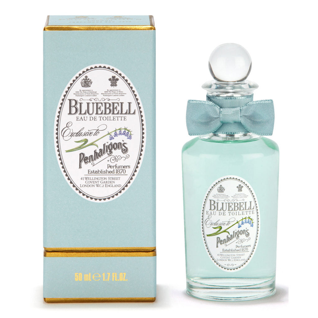 A bright blue bottle of perfule with a decorative vintage-style logo and blue bow, next to its blue vintage-style box