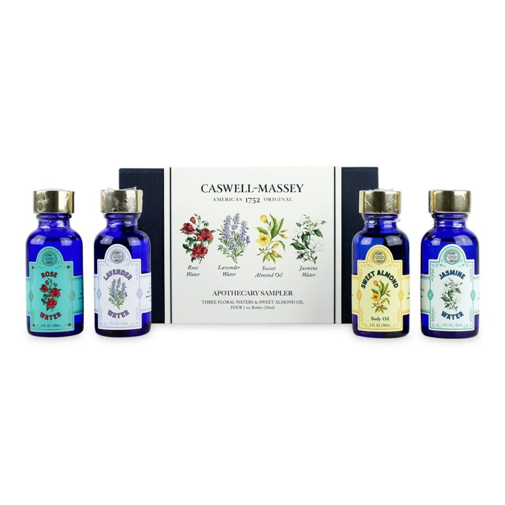 Four small blue bottles with floral illustrations on the label and a blue box decorated with floral illustrations and the Caswell-Massey logo