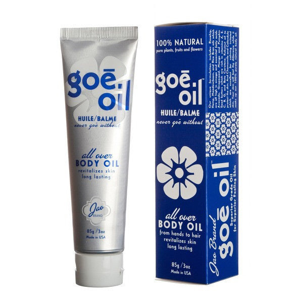 A silver tube of Goe Oil decorated with blue text and and white flowers, next to a blue box decorated with white text and white flowers