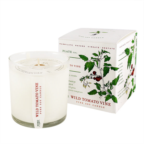 A round white Kobo candle next to its white box decorated with a drawing of a tomato vine
