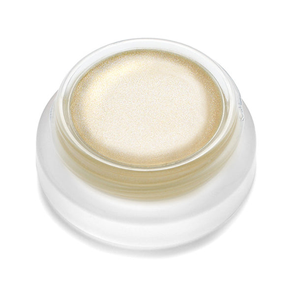 A small clear pot with twist-off lid filled with light gold-colored RMS Living Luminizer highlighters