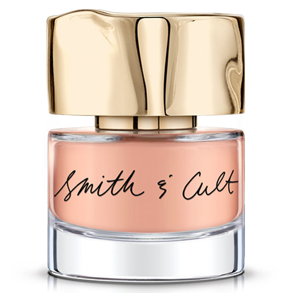 A bottle of peach-colored Smith + Cult nail polish with a hammered gold lid