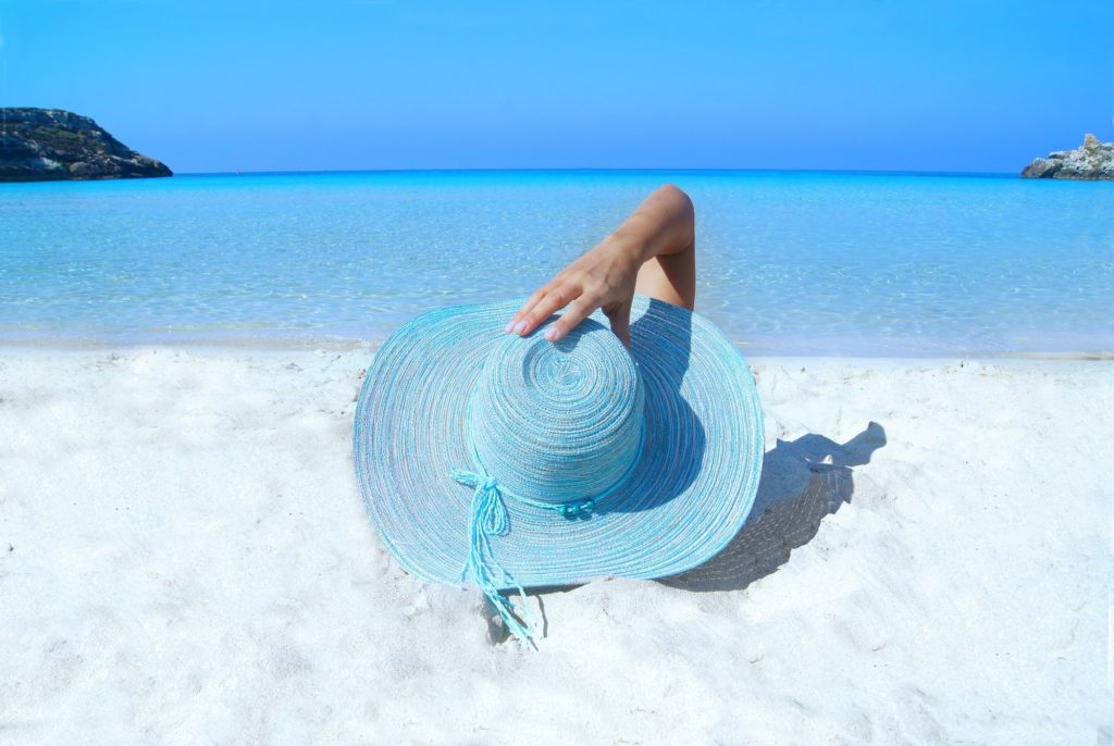 A woman with a bright blue sun hat lays on the beach