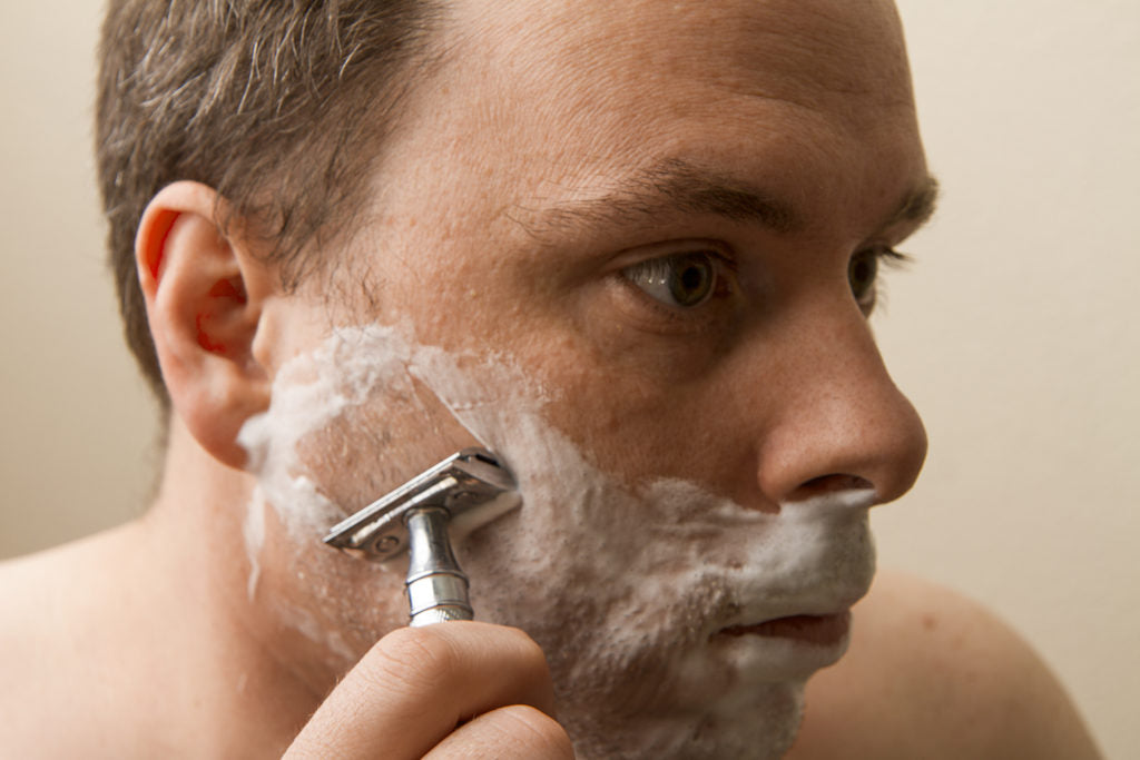 A man shaving with a traditional single-edge safety razor