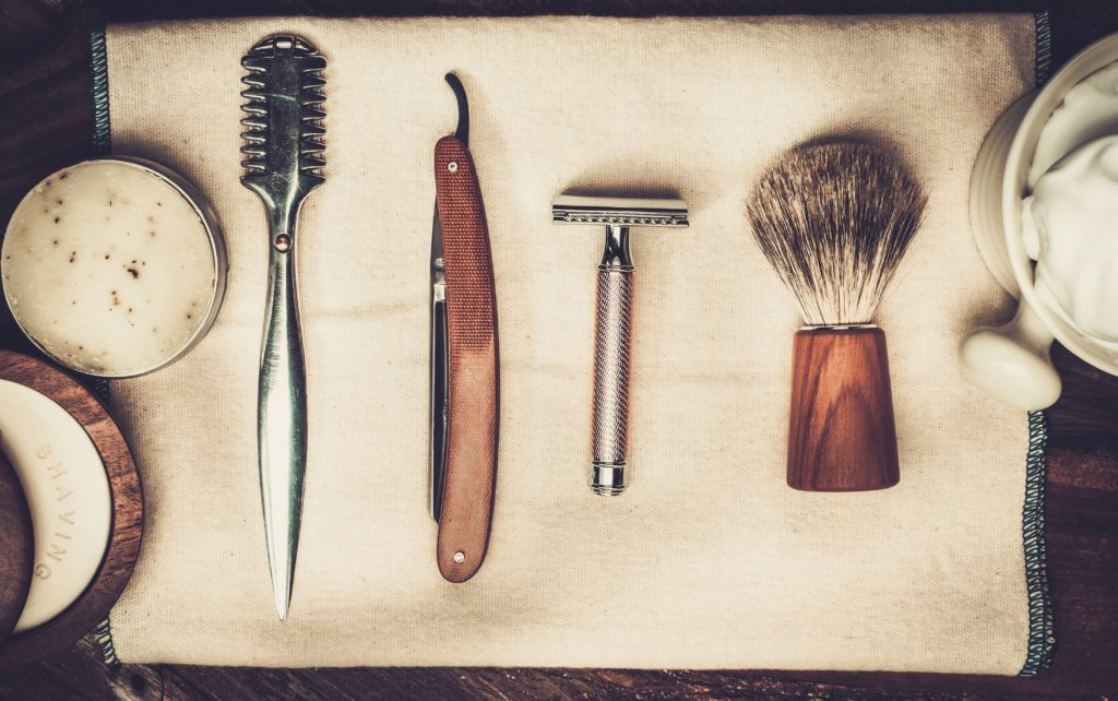 Several traditional wet shaving tools including a straight razor, safety razor, shave brush, and lather mug